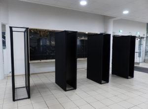Lahden pääkirjaston aulan näyttelykalusteet: iso lasivitriini seinällä ja 4 kaksipuoleista näyttelysermiä.