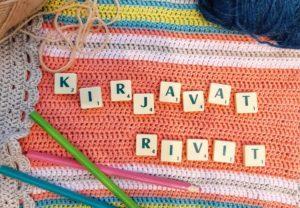 Värikästä neuletta, puuvärejä ja Scrabble-pelin kirjainlaattoja.