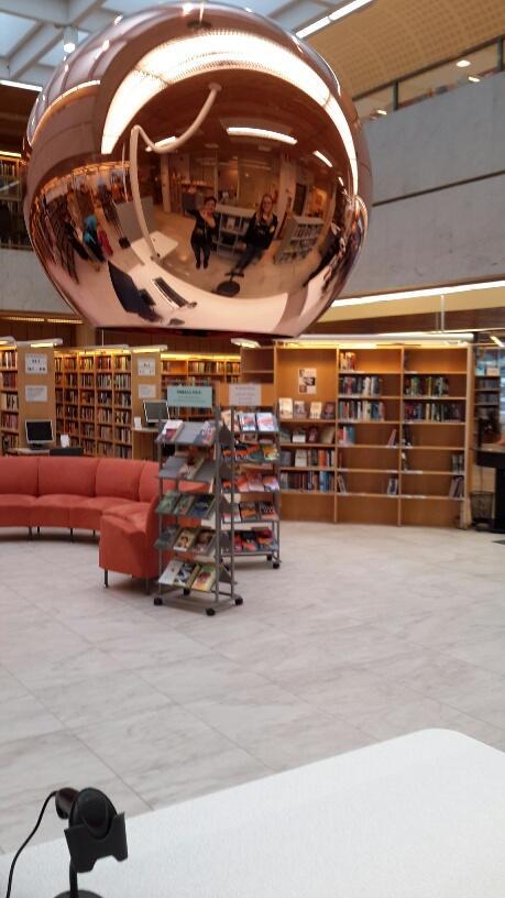 Kirjaston sisätilassa pyöreä kuparinen lampunkupu hallistsee etualaa, sohva, palautushylly.