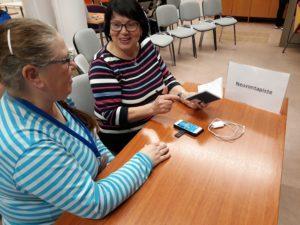 """Pöydän ääressä kaksi naista juttelee, pöydällä älypuhelin ja laturi sekä juliste, jossa lukee """"neuvontapiste""""."""
