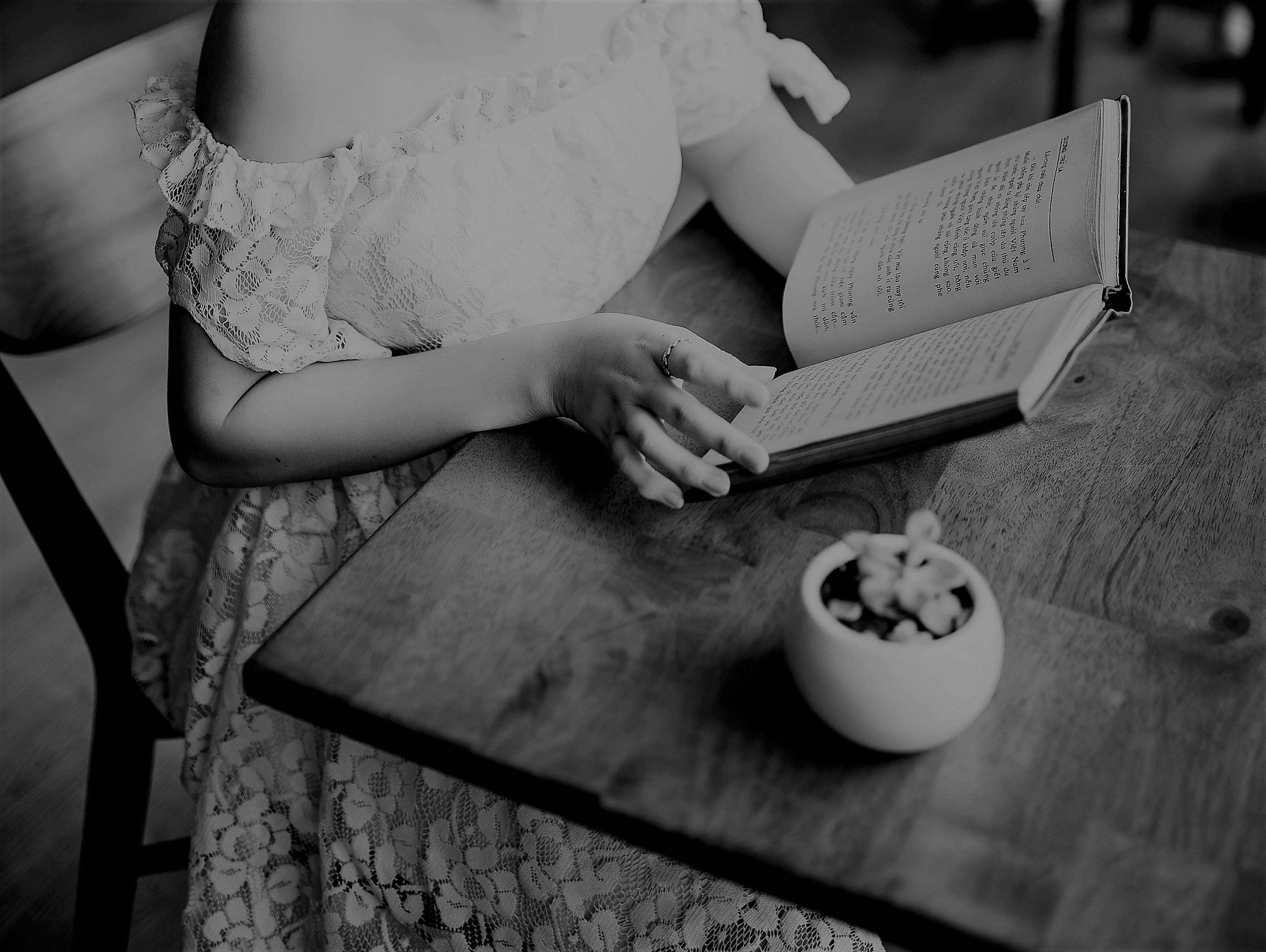 Henkilö lukee kirjaa pitsimekko yllään mustavalkokuvasssa, Henkilön kasvot jäävät kuvan ulkopuolelle.