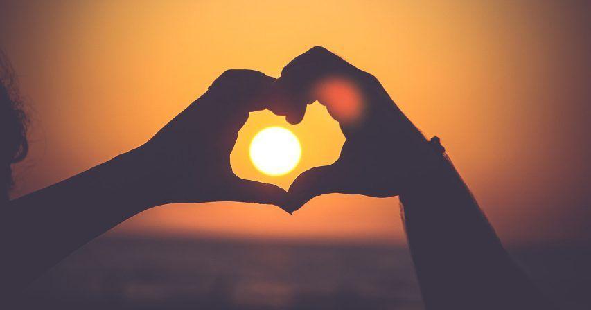 Käsillä muodostettu sydän kehystää laskevaa aurinkoa.