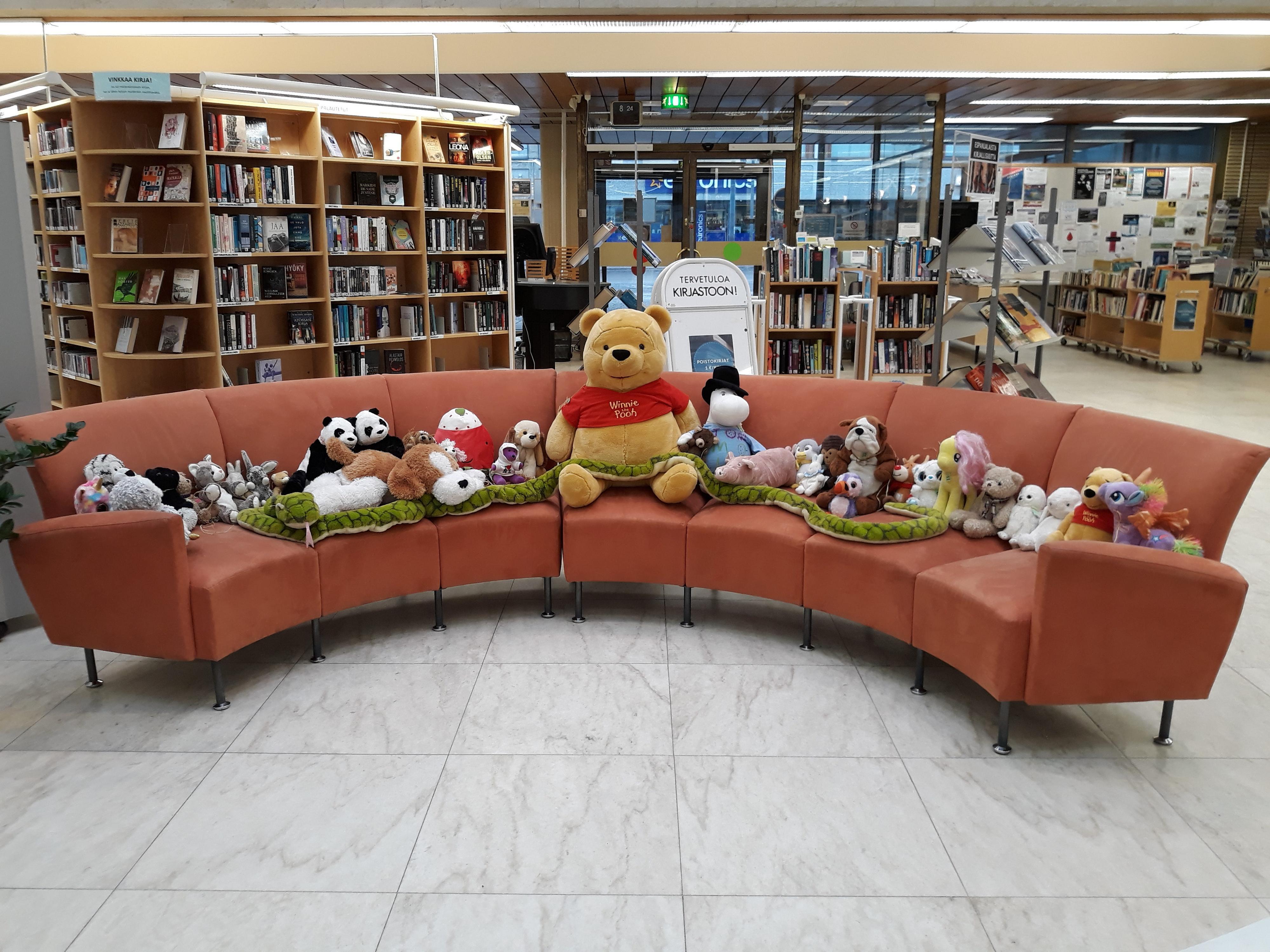 Paljon pehmoleluja ryhmiteltynä istumaan kirjaston kaarisohvalle.