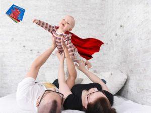Vanhemmat pitävät kirjaa tavoittelevaa vauvaa, jolla on lepattava viitta yllään.