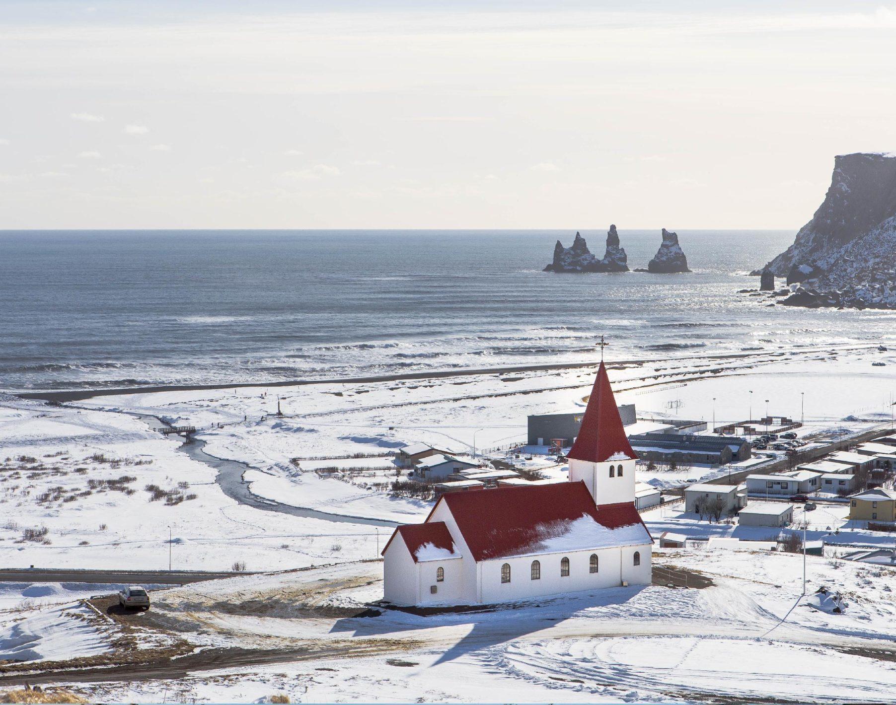 Punakattoinen valkoinen kirkko lumisella merenrannalla.
