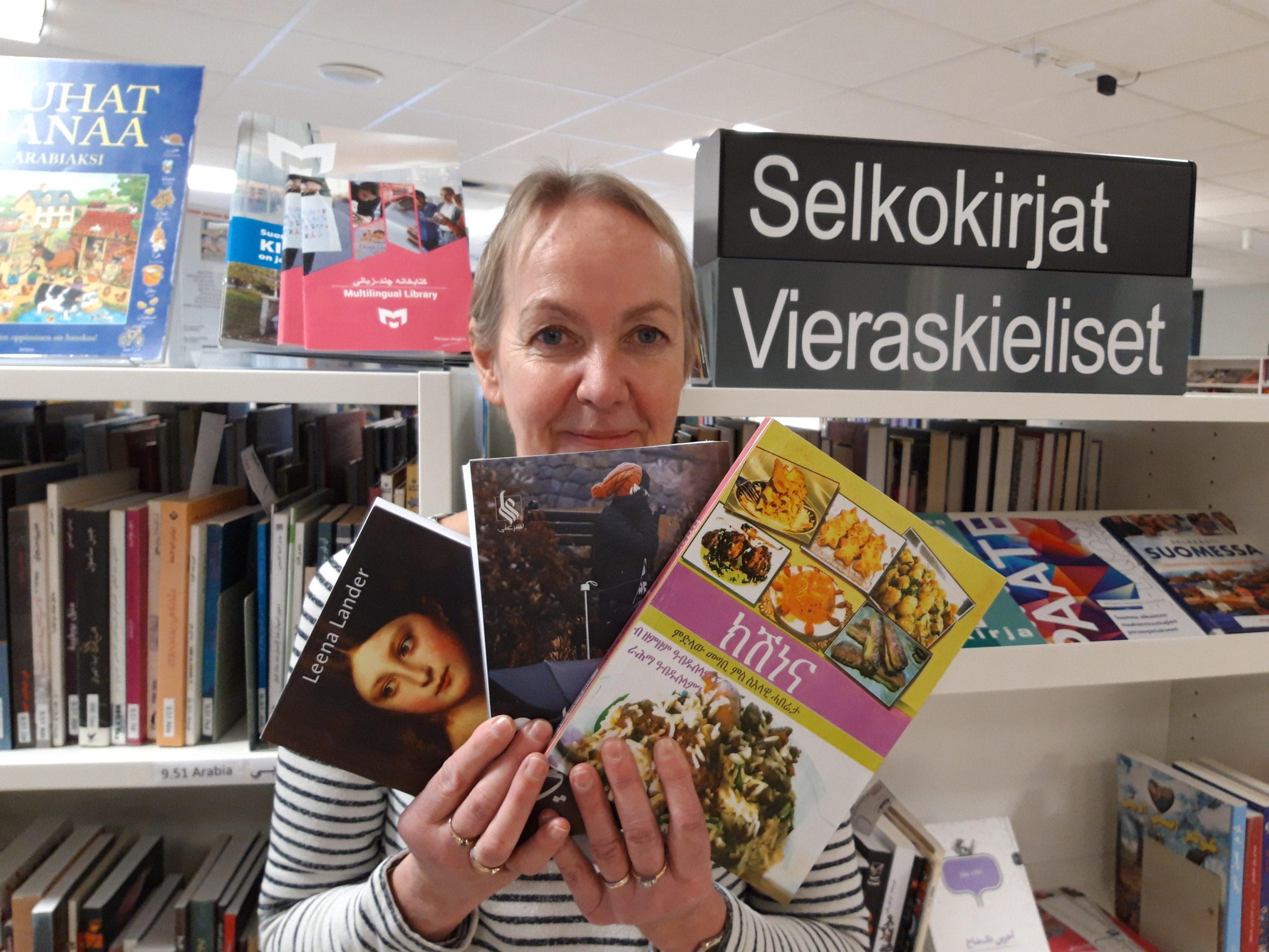 nainen vieraskielisiä kirjoja kädessään