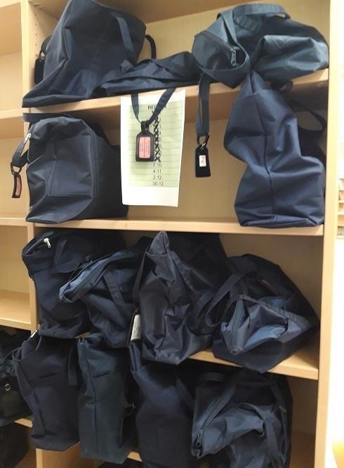 Mustia kirjakasseja kirjahyllyssä odottamassa kuljetusta.