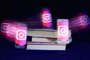 Kuvassa Instagram-logot leijuvat kirjapinon ympärillä.