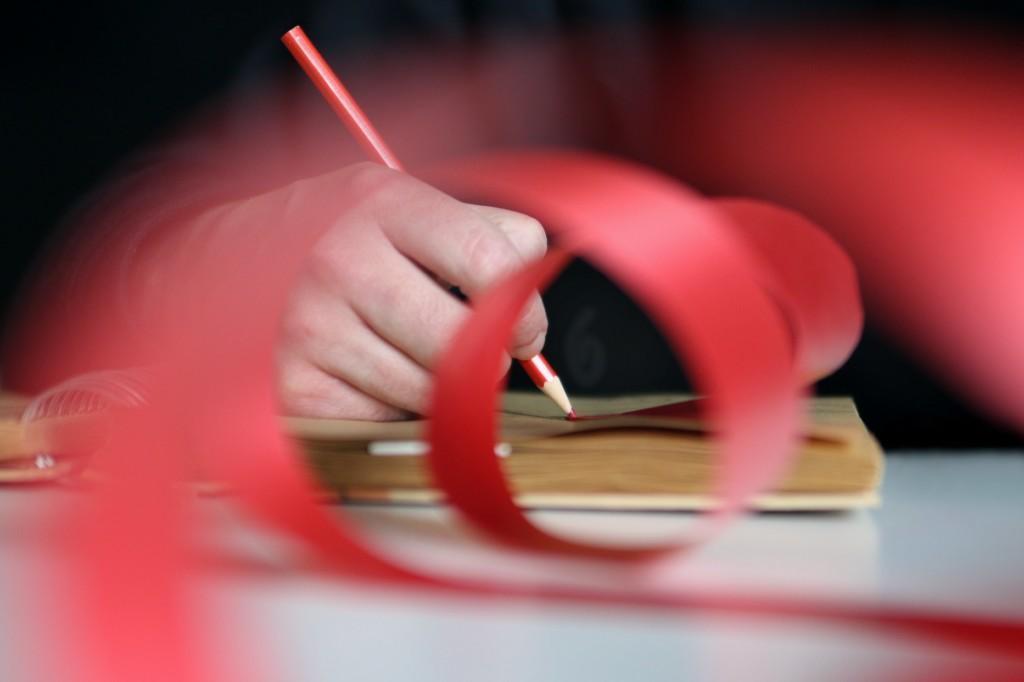 Kirjoittava käsi jonka edessä punainen nauha.