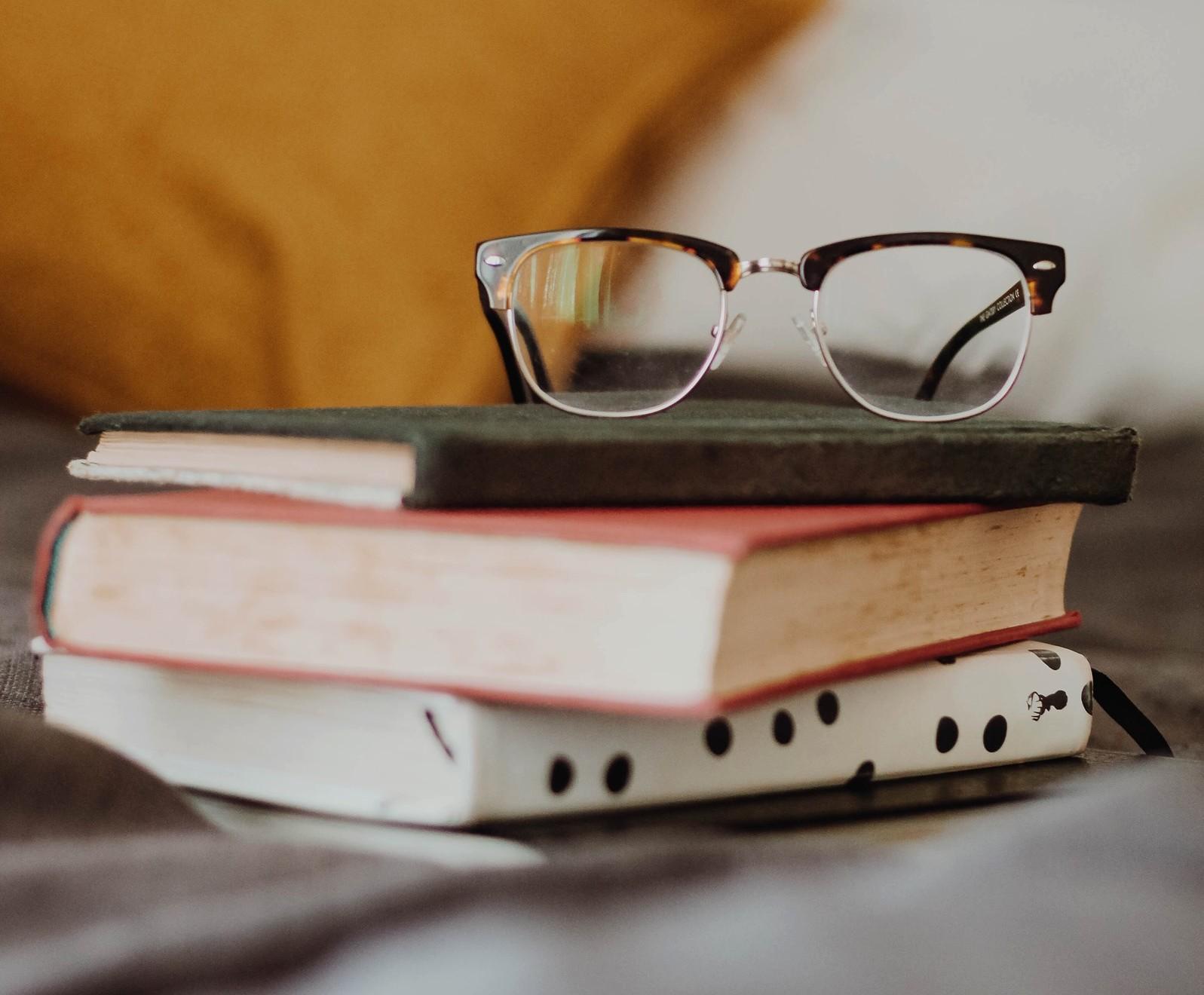 Kolme kirjaa pinossa, päällä silmälasit ja taustalla tyyny.