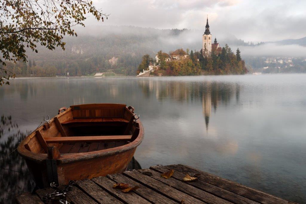 Vene, sumuinen tyyni vesi ja saari jossa korkea torni.