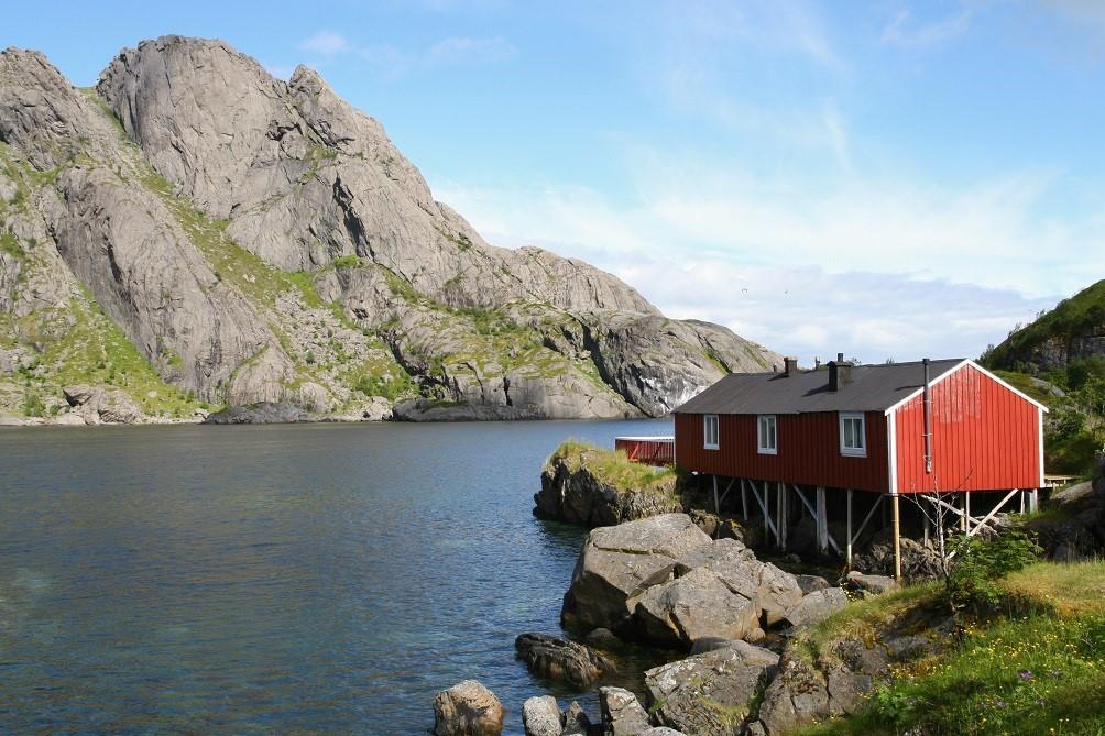 Punainen mökki Pohjois-Norjan rannikkomaisemissa